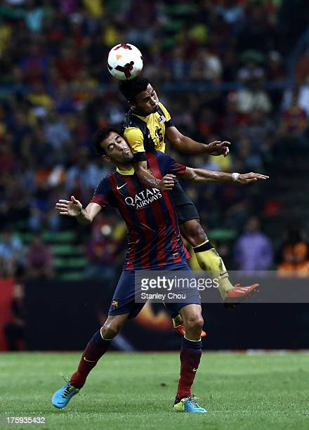 Sergio Busquets of Barcelona FC clashes with Putera Nadher of Malaysia during the friendly match between FC Barcelona and Malaysia at Shah Alam...