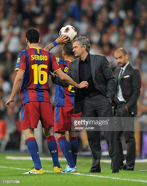 Sergio Busquets of Barcelona holds head coach Jose Mourinho of Real Madrid by his shirt as they chat while head coach Josep Guardiola of Barcelona...