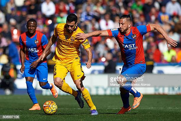 Sergio Busquets of Barcelona is tackled by Ghilas of Levante during the La Liga match between Levante UD and FC Barcelona at Ciutat de Valencia on...