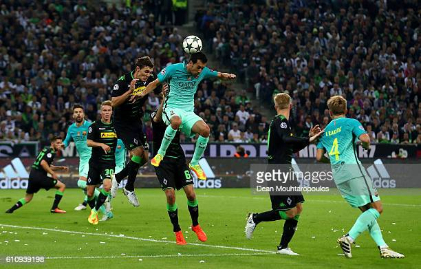 Sergio Busquets of Barcelona jumps for the ball with Andreas Christensen and Christoph Kramer of Borussia Moenchengladbach during the UEFA Champions...