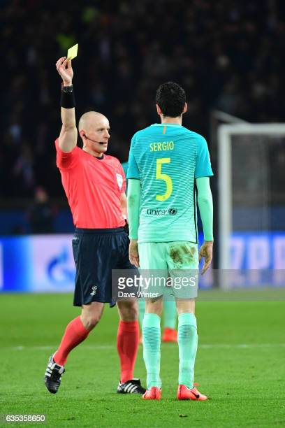 Sergio Busquets of Barcelona receives a yellow card from referee Szymon Marciniak during the Champions League match between Paris Saint Germain and...
