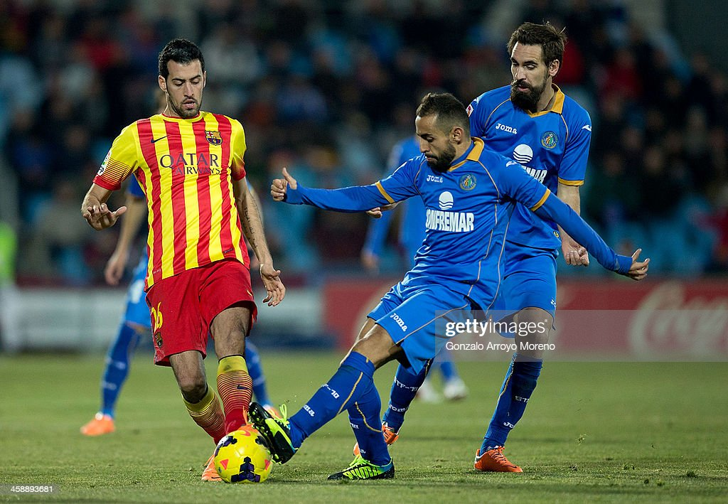 <a gi-track='captionPersonalityLinkClicked' href=/galleries/search?phrase=Sergio+Busquets&family=editorial&specificpeople=5477015 ng-click='$event.stopPropagation()'>Sergio Busquets</a> (L) of FC Barcelona competes for the ball with Diego Castro (R) of Getafe CF during the La Liga match between Getafe CF and FC Barcelona at Coliseum Alfonso Perez on December 22, 2013 in Getafe, Spain.