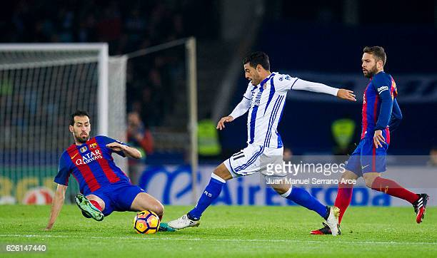 Sergio Busquets of FC Barcelona duels for the ball with Carlos Vela of Real Sociedad during the La Liga match between Real Sociedad de Futbol and FC...