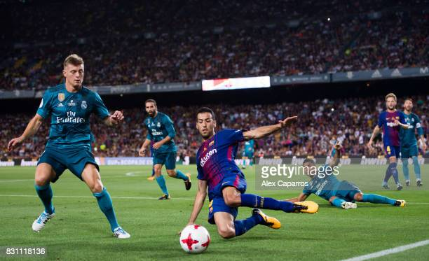 Sergio Busquets of FC Barcelona plays the ball next to Toni Kroos of Real Madrid CF during the Supercopa de Espana Supercopa Final 1st Leg match...