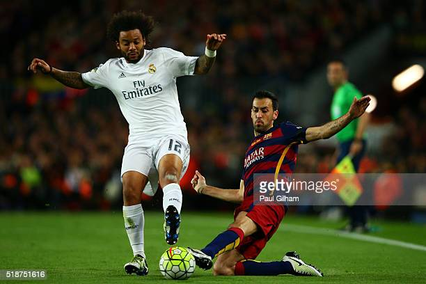 Sergio Busquets of FC Barcelona slides in on Marcelo of Real Madrid CF during the La Liga match between FC Barcelona and Real Madrid CF at Camp Nou...