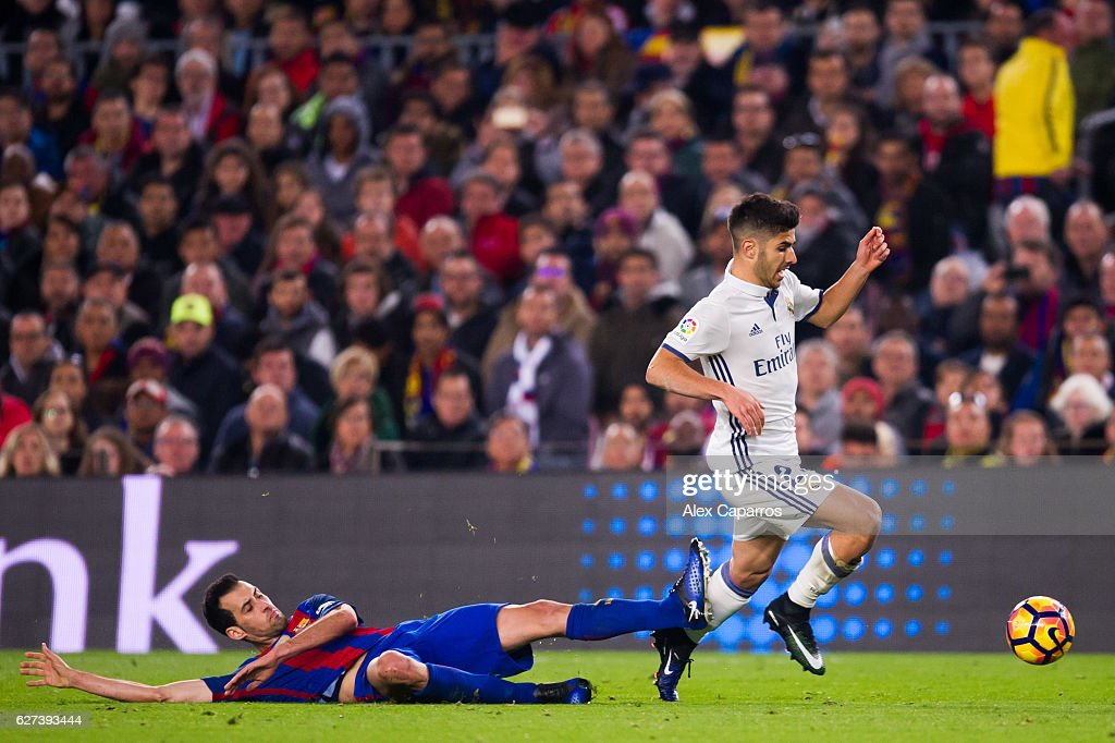 Sergio Busquets of FC Barcelona tackles Marco Asensio of Real Madrid CF during the La Liga match between FC Barcelona and Real Madrid CF at Camp Nou...