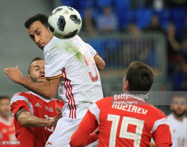 Sergio Busquets of Spain in action against Fedor Kudryashov and Daler Kuzyaev of Russia during an international friendly football match between...