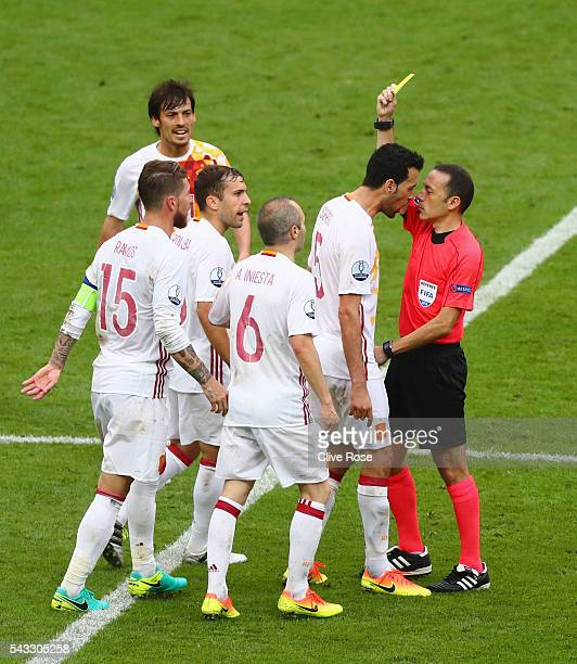 Sergio Busquets of Spain is shown a yellow card by referee Cuneyt Cakir during the UEFA EURO 2016 round of 16 match between Italy and Spain at Stade...
