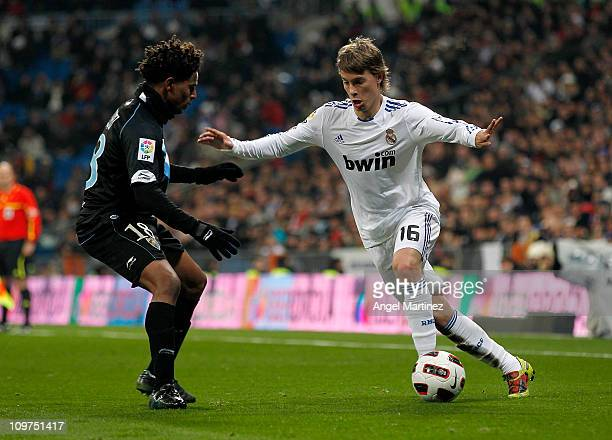 Sergio Canales of Real Madrid is challenged by Eliseu Pereira of Malaga during the La Liga match between Real Madrid and Malaga at Estadio Santiago...
