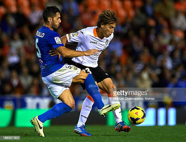 Sergio Canales of Valencia competes for the ball with Angel Trujillo of Almeria during the La Liga match between Valencia CF and UD Almeria at...