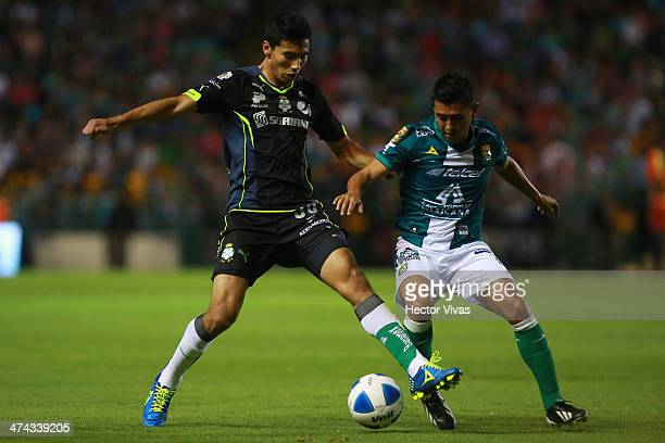 Sergio Ceballos of Santos struggles for the ball with Elias Hernandez of Leon during a match between Leon and Santos Laguna as part of the Clausura...