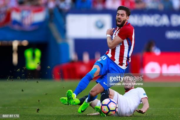 Sergio Escudero of Sevilla FC tackles Yannick Carrasco of Atletico de Madrid during the La Liga match between Club Atletico de Madrid and Sevilla FC...