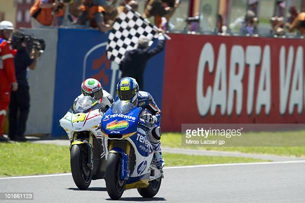 Sergio Gadea of Spain and Tenerife 40 Pons cuts the finish lane in front of Simone Corsi of Italy and JIR Moto2 at the end of Moto2 race of Grand...