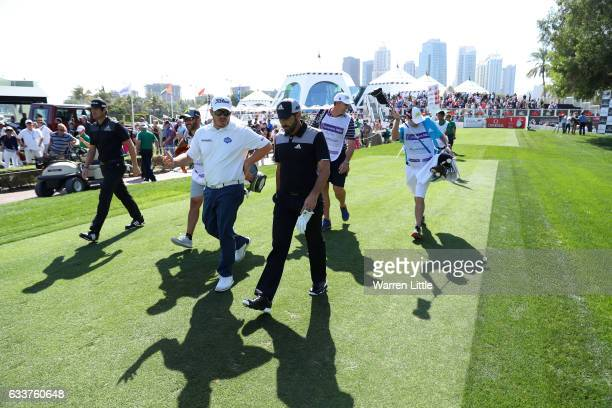 Sergio Garcia and Nacho Elvira of Spain walk off the 1st tee with George Coetzee of South Africa during the third round of the Omega Dubai Desert...