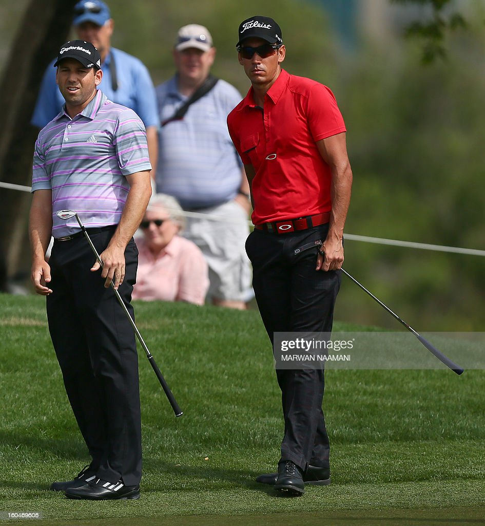 Sergio Garcia of Spain (L) and his countryman Rafa Cabrera-Bello line a putt during the second round of the Dubai Desert Classic golf tournament in the Gulf emirate of Dubai on February 1, 2013. AFP PHOTO/MARWAN NAAMANI