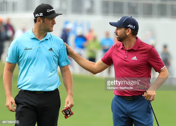 Sergio Garcia of Spain and Jon Rahm of Spain talk after putting on the 13th hole of their match during round three of the World Golf...