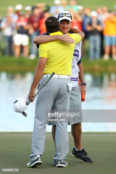 Sergio Garcia of Spain celebrates his victory on the 18th green with caddie Glenn Murray during the final round of the Omega Dubai Desert Classic at...