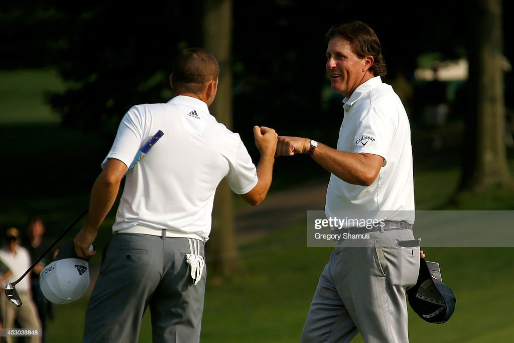 Sergio Garcia of Spain (L) is congratulated by Phil Mickelson after a birdie putt on the 18th green during the second round of the World Golf Championships-Bridgestone Invitational at Firestone Country Club South Course on August 1, 2014 in Akron, Ohio.