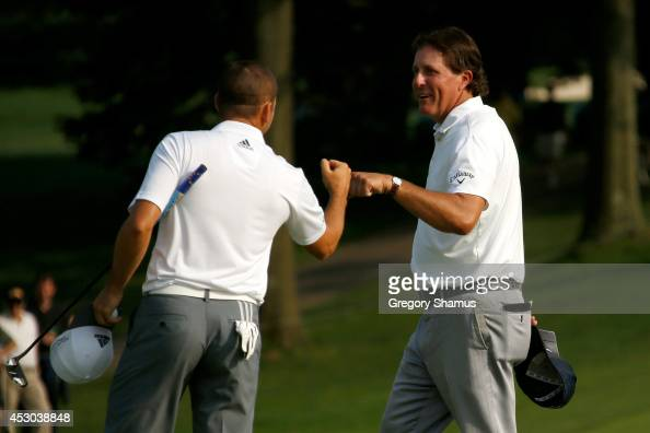 Sergio Garcia of Spain is congratulated by Phil Mickelson after a birdie putt on the 18th green during the second round of the World Golf...