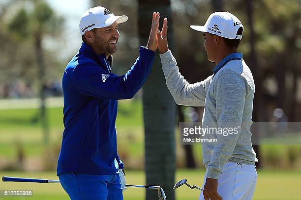 Sergio Garcia of Spain is congratulated by Rickie Fowler of the United States after holing out for eagle on the second hole during the first round of...