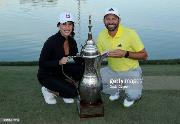 Sergio Garcia of Spain poses with the trophy and his fiancee Angela Akins after his two shot victory during the final round of the 2017 Omega Dubai...
