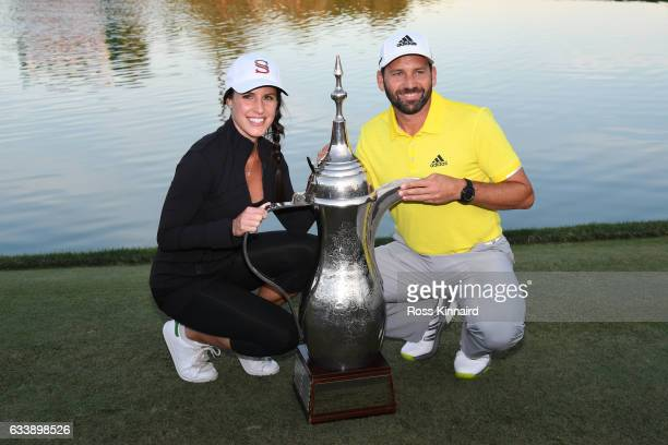 Sergio Garcia of Spain poses with the trophy and his girlfriend Angela Akins following his victory during the final round of the Omega Dubai Desert...