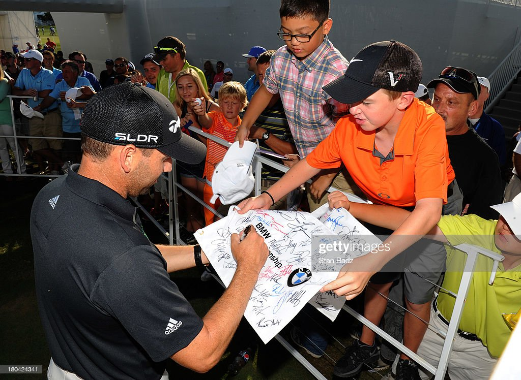 Sergio Garcia of Spain signs autographs for fans after the first round of the BMW Championship at Conway Farms Golf Club on September 12, 2013 in Lake Forest, Illinois.