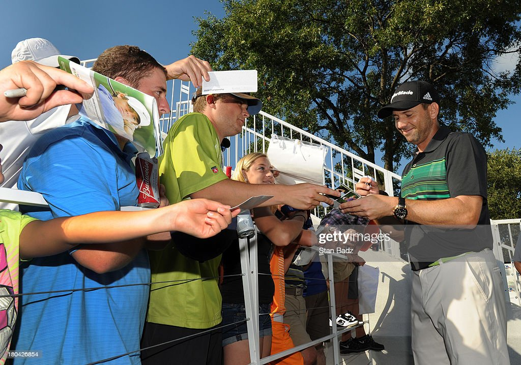 Sergio Garcia of Spain signs autographs for fans during the first round of the BMW Championship at Conway Farms Golf Club on September 12, 2013 in Lake Forest, Illinois.