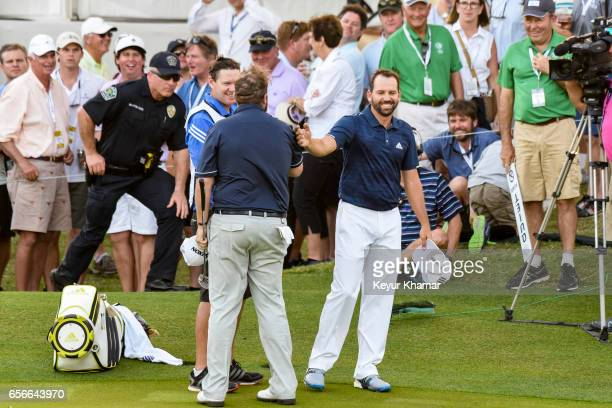Sergio Garcia of Spain smiles as he shakes hands with Shane Lowry of Ireland following their halved match on the 18th hole green during round one of...