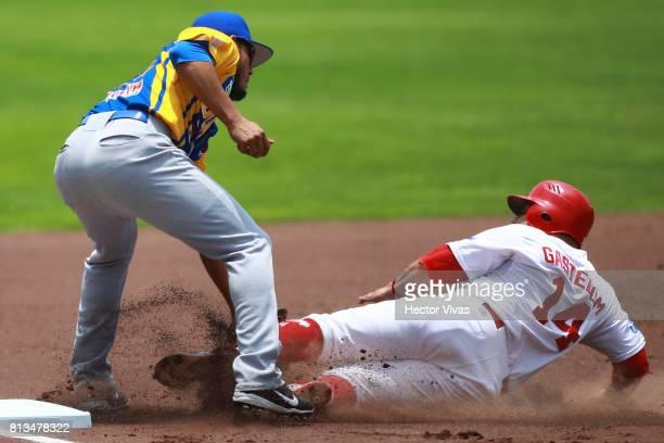 Sergio Gastelum of Diablos Rojos is tagged out in third base by Yosshel Hurtado of Olmecas during the match between Olmecas de Tabasco and Diablos...