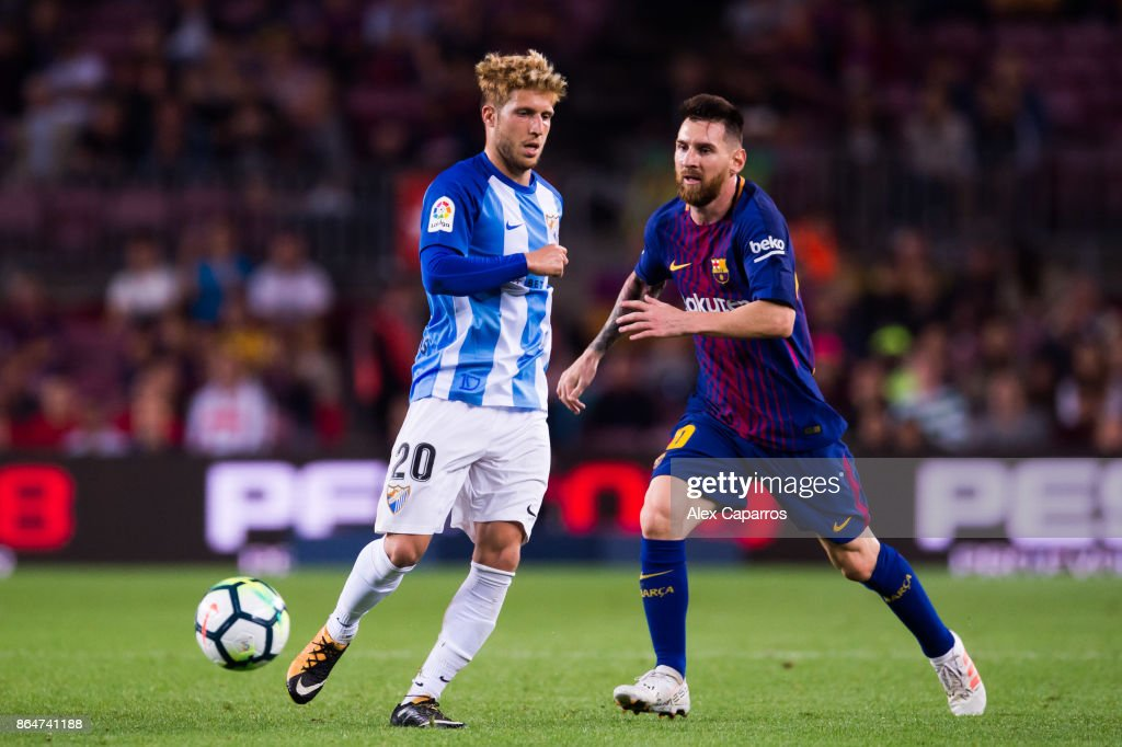 Sergio Gontan 'Keko' of Malaga CF plays the ball past Lionel Messi of FC Barcelona during the La Liga match between Barcelona and Malaga at Camp Nou on October 21, 2017 in Barcelona, Spain.