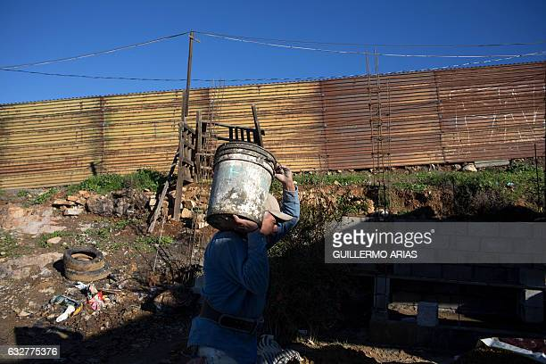 Sergio Gonzalez works on his daughter's house near the US Mexico border fence at El Nido del Aguila on the outskirts of Tijuana on Jan 26 in...