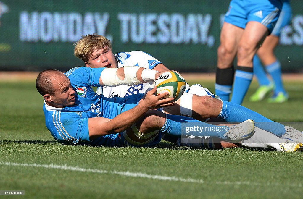 <a gi-track='captionPersonalityLinkClicked' href=/galleries/search?phrase=Sergio+Parisse&family=editorial&specificpeople=648570 ng-click='$event.stopPropagation()'>Sergio Parisse</a> of Italy (L) presents the ball in the tackle during the Castle Larger Incoming Tour match between Italy and Scotland at Loftus Versfeld on June 22, 2013 in Pretoria, South Africa.