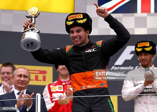 Sergio Perez of Mexico and Force India celebrates on the podium next to the President of Russia Vladimir Putin Sebastian Vettel of Germany and...