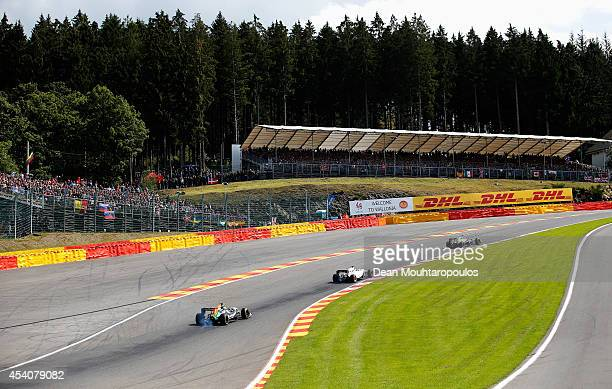 Sergio Perez of Mexico and Force India Felipe Massa of Brazil and Williams and Jenson Button of Great Britain and McLaren drive during the Belgian...