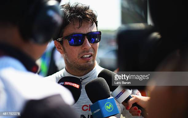 Sergio Perez of Mexico and Force India speaks with members of the media as he returns to the pit lane after crashing during practice for the Formula...