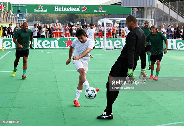Sergio Perez of Mexico and Force India takes a shot against Dida of Brazil during the Heineken Champions of the Grid Charity football match during...