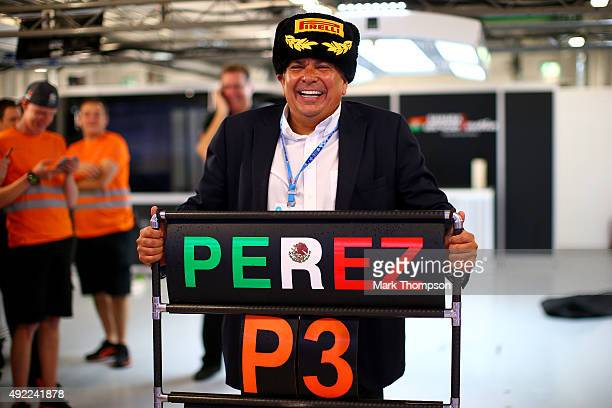 Sergio Perez of Mexico and Force India's father Antonio Perez Garibay celebrates in the team garage after his son finished third in the Formula One...