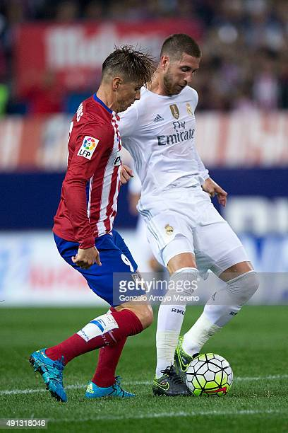 Sergio Ramos of Real Madrid CF competes for the ball with Fernando Torres of Atletico de Madrid during the La Liga match between Club Atletico de...