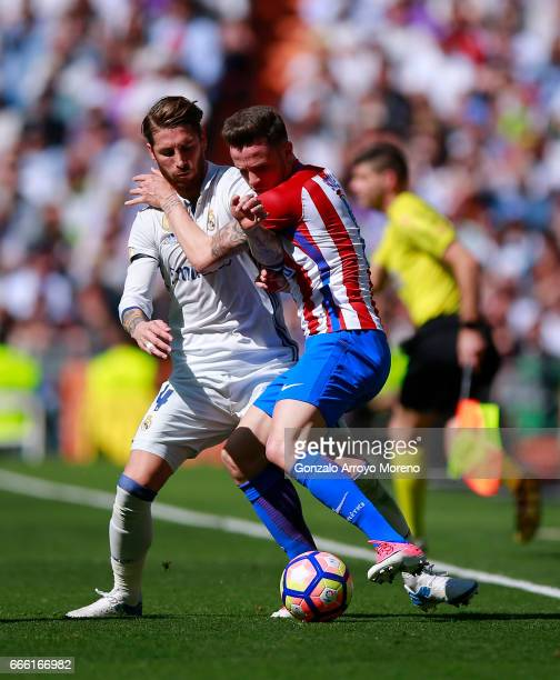 Sergio Ramos of Real Madrid CF competes for the ball with Saul Niguez of Atletico de Madrid during the La Liga match between Real Madrid CF and Club...