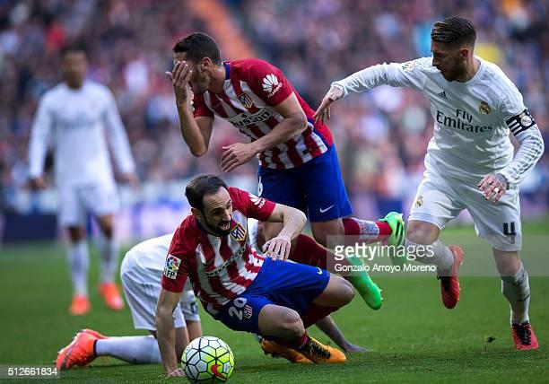 Sergio Ramos of Real Madrid CF tackles Koke of Atletico de Madrid as his teammate Juan Francisco Torres alias Juanfran falls during the La Liga match...