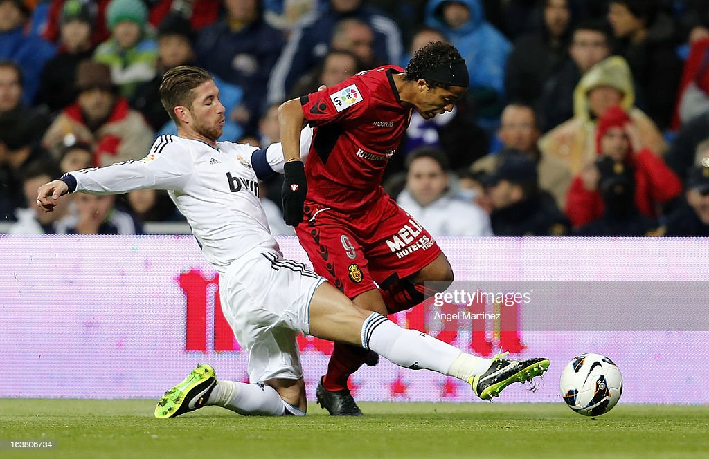 Sergio Ramos of Real Madrid challenges Giovani dos Santos of Mallorca during the La Liga match between Real Madrid and RCD Mallorca at Estadio Santiago Bernabeu on March 16, 2013 in Madrid, Spain.