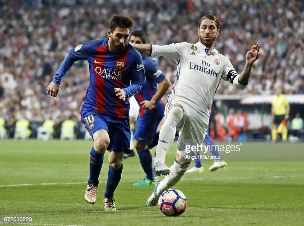 Sergio Ramos of Real Madrid competes for the ball with Lionel Messi of FC Barcelona during the La Liga match between Real Madrid and FC Barcelona at...