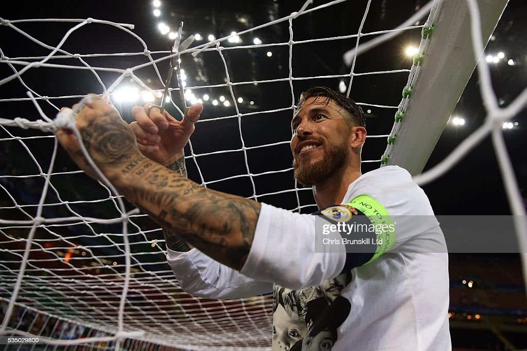 Sergio Ramos of Real Madrid cuts the goal netting following the UEFA Champions League Final between Real Madrid and Club Atletico de Madrid at Stadio Giuseppe Meazza on May 28, 2016 in Milan, Italy.