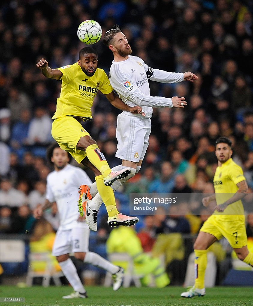 Sergio Ramos of Real Madrid goes for a high ball against Cedric Bakambu of Villarreal CF during the La Liga match between Real Madrid and Villarreal at Estadio Santiago Bernabeu on April 20, 2016 in Madrid, Spain.