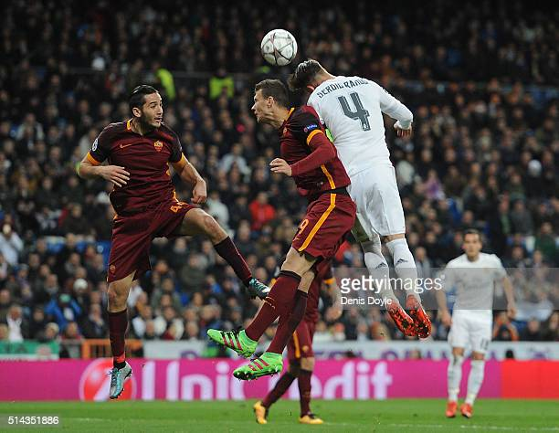 Sergio Ramos of Real Madrid goes for a high ball against Kostas Manolas and Edin Dzeko of AS Roma during the UEFA Champions League Round of 16 Second...