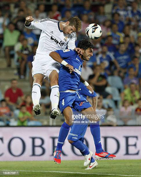 Sergio Ramos of Real Madrid heads the ball against Miguel Torres of Getafe during the La Liga match between Getafe and Real Madrid at Coliseum...