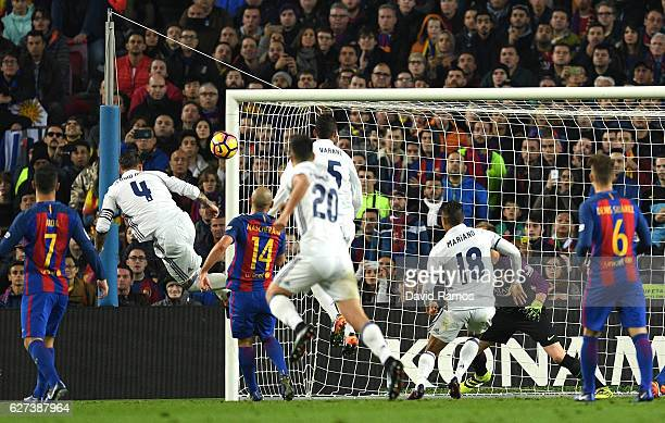 Sergio Ramos of Real Madrid heads to score his team's first goal during the La Liga match between FC Barcelona and Real Madrid CF at Camp Nou on...