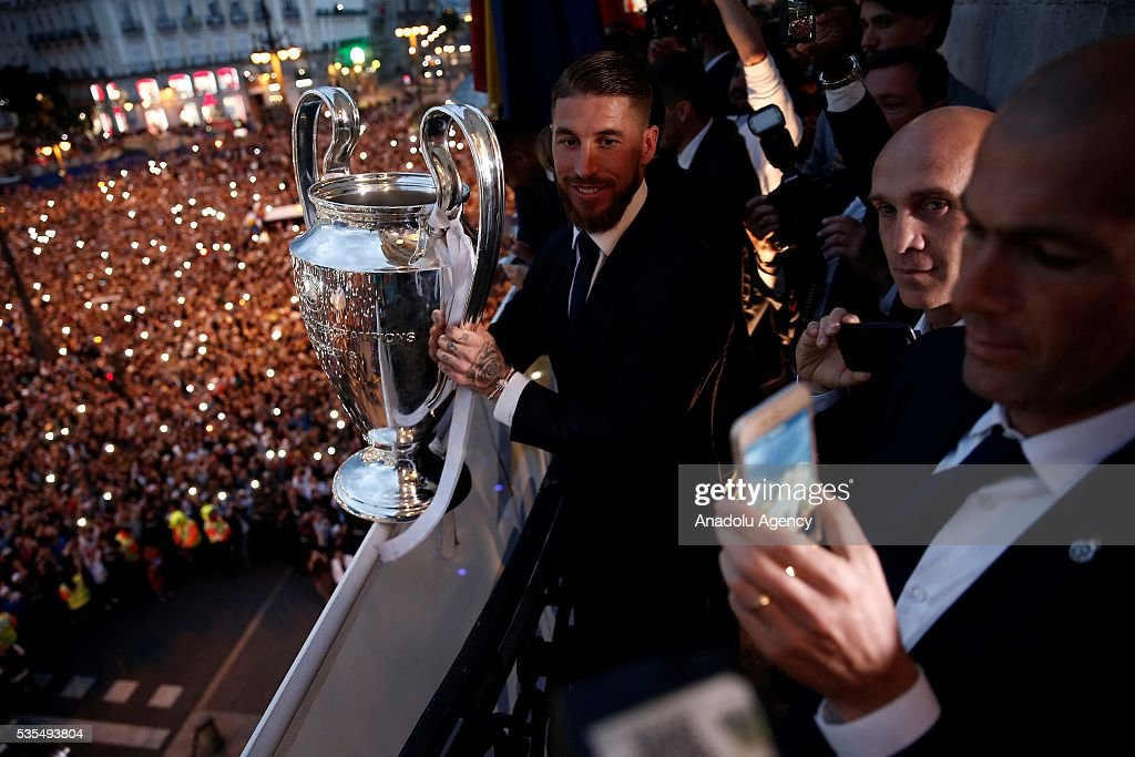 Sergio Ramos (L) of Real Madrid holds the trophy during their visit to President of the Community of Madrid Cristina Cifuentes after Real Madrid won the UEFA Champions League Final match against Club Atletico de Madrid, at Madrid City Hall in Madrid, Spain on May 29, 2016.
