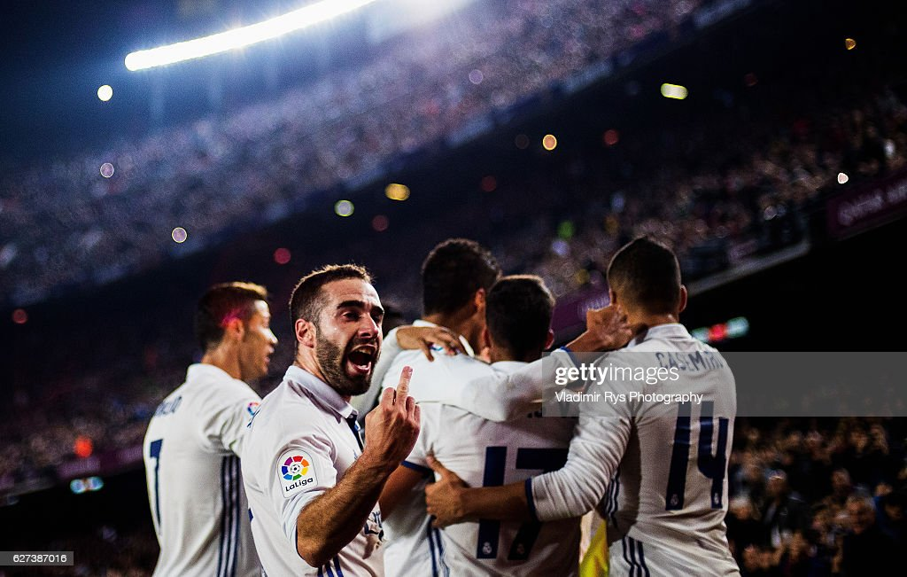 Sergio Ramos of Real Madrid is celebrated by his team after scoring the 11 goal as his team mate Daniel Carvajal gestures towards the fans during the...